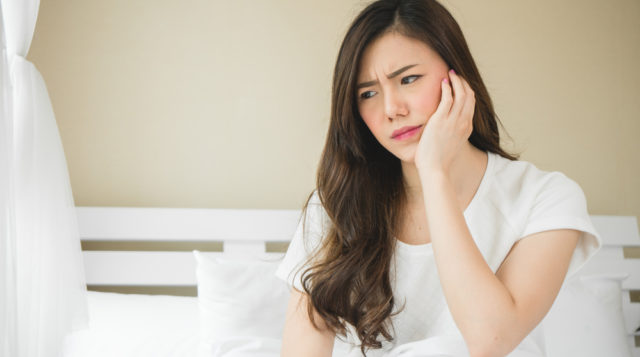 Teenager suffering from bruxism with sore jaw touching her cheek.